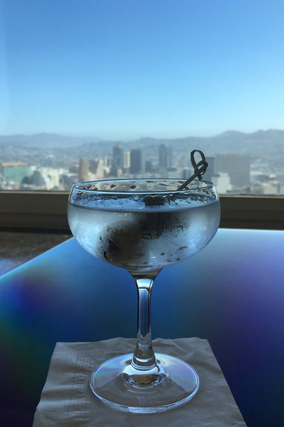 Martini in foreground with backed by highrise view out window