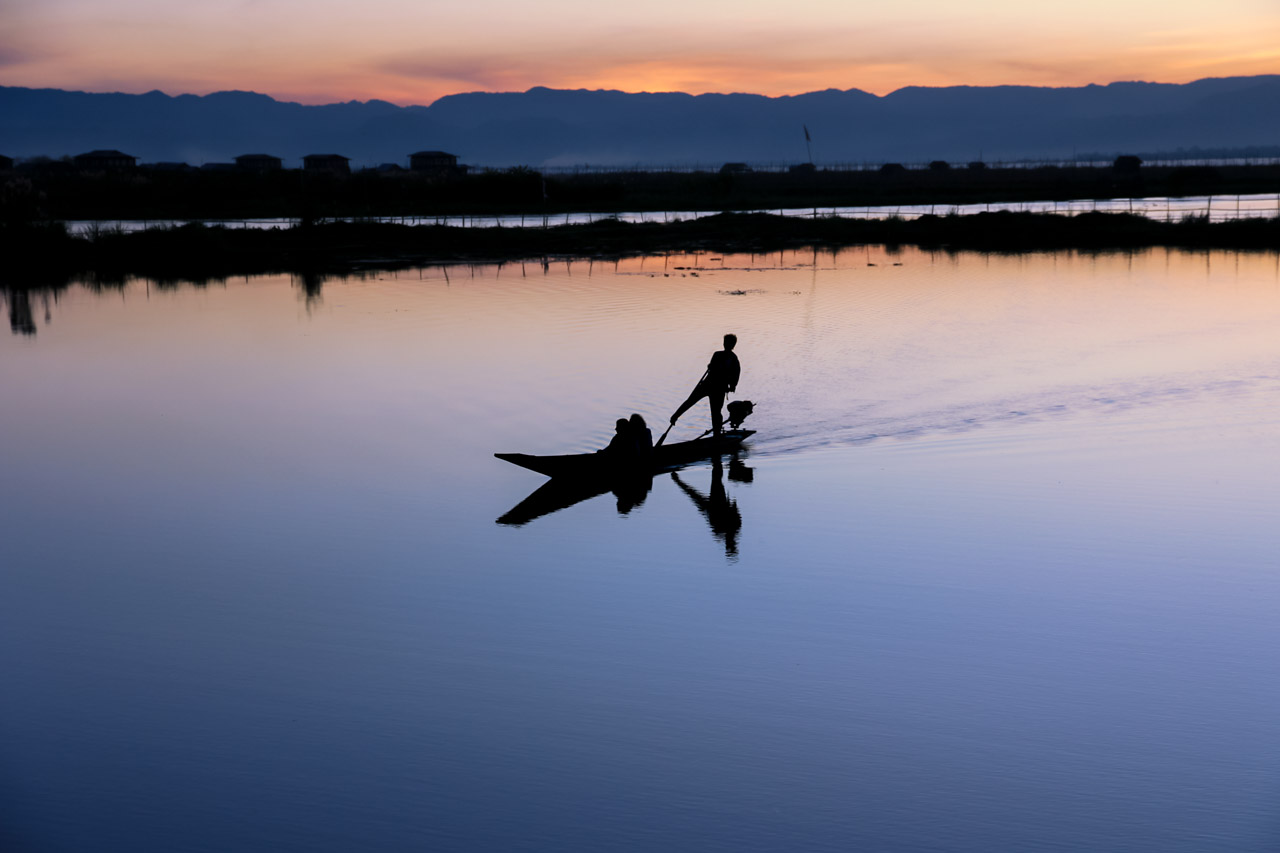 Silhouette of man standing on a boat with sunset reflected in the glassy water