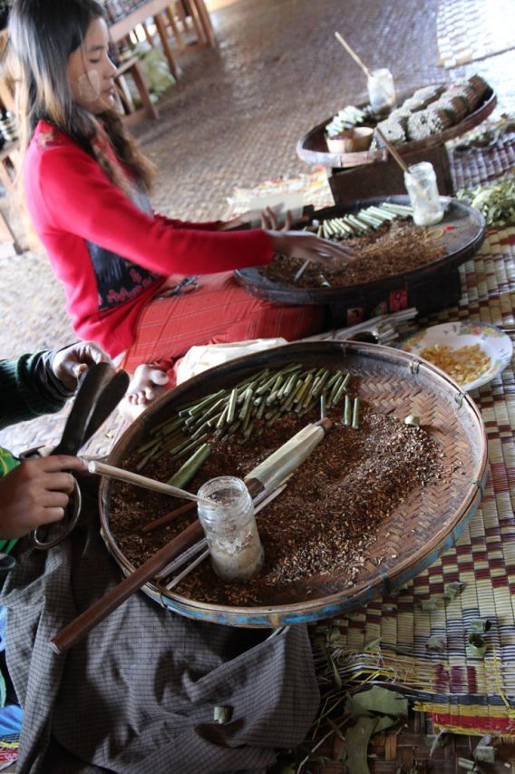 Women hand rolling cigars with large, flat baskets of ingredients