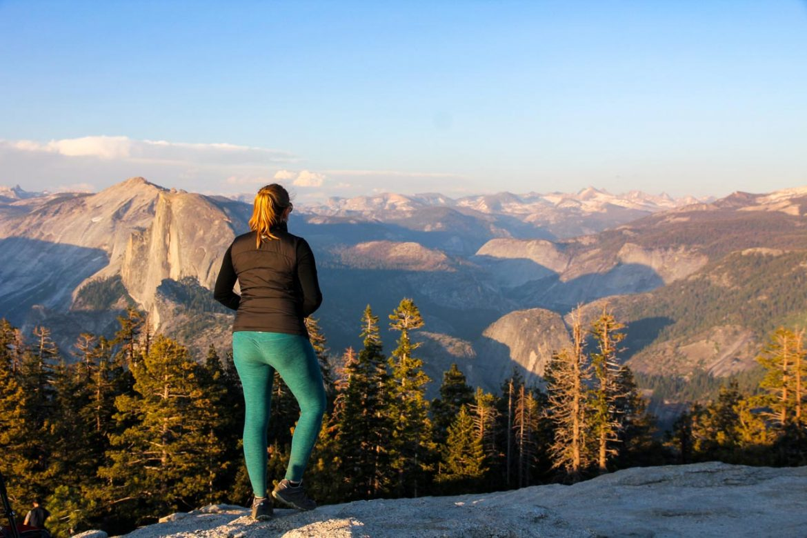 Woman looking out over valleys and mountains in warm sunset light