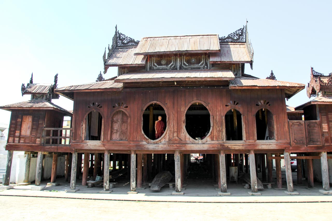 Shwe Yan Pyay monastery exterior - teak building on stilts with oval and arched windows and decorative elements on roof