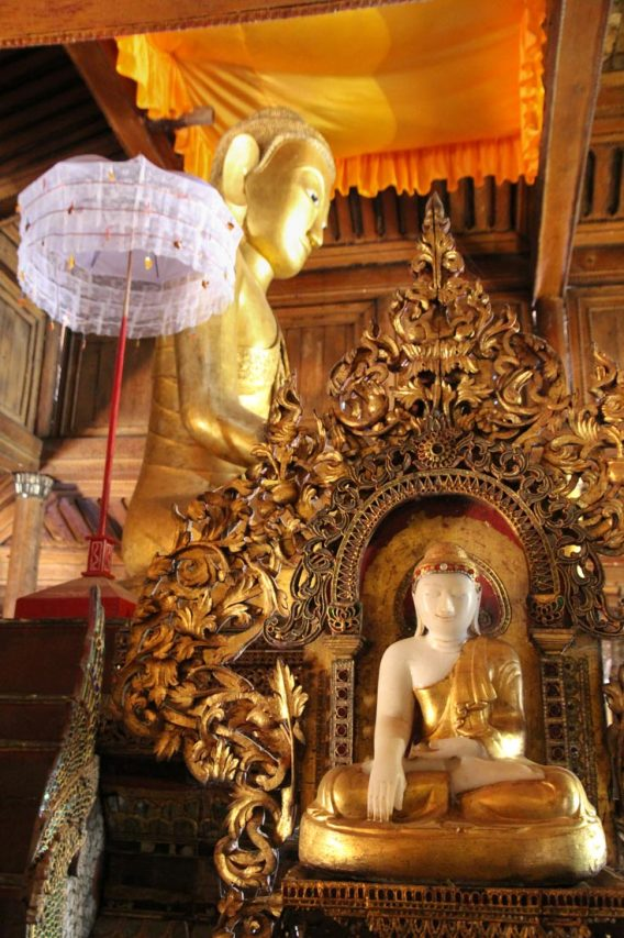 Buddha images in gold with white parasol