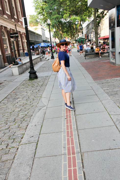 Woman in blue standing on Boston's Freedom Trail, red brick line