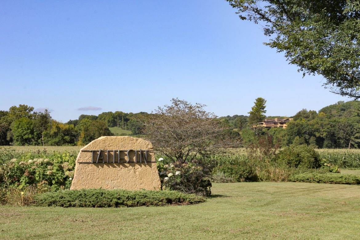 "Stone sign reading ""Taliesin"" with large home on hill in the background"
