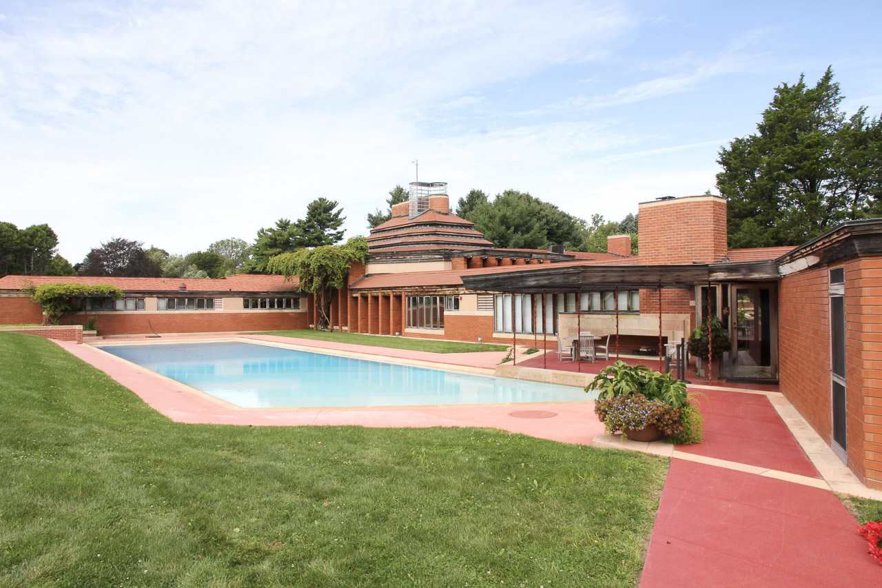 Image of large modernist brick home with pool in foreground