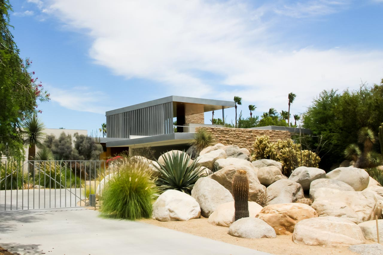Two story modernist home with boulder and succulent garden in foreground