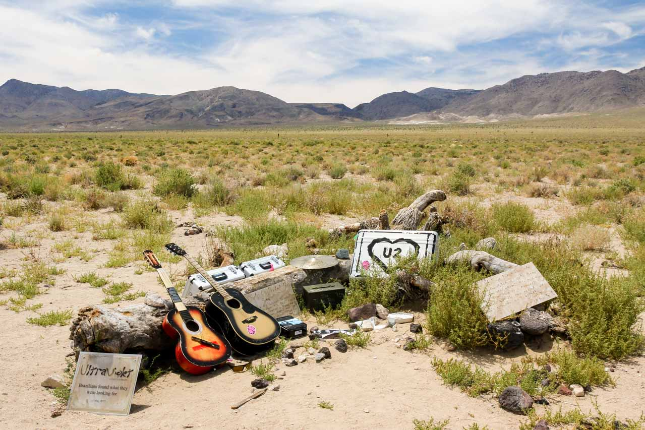 Fallen tree with fan tributes including guitars and roadcases