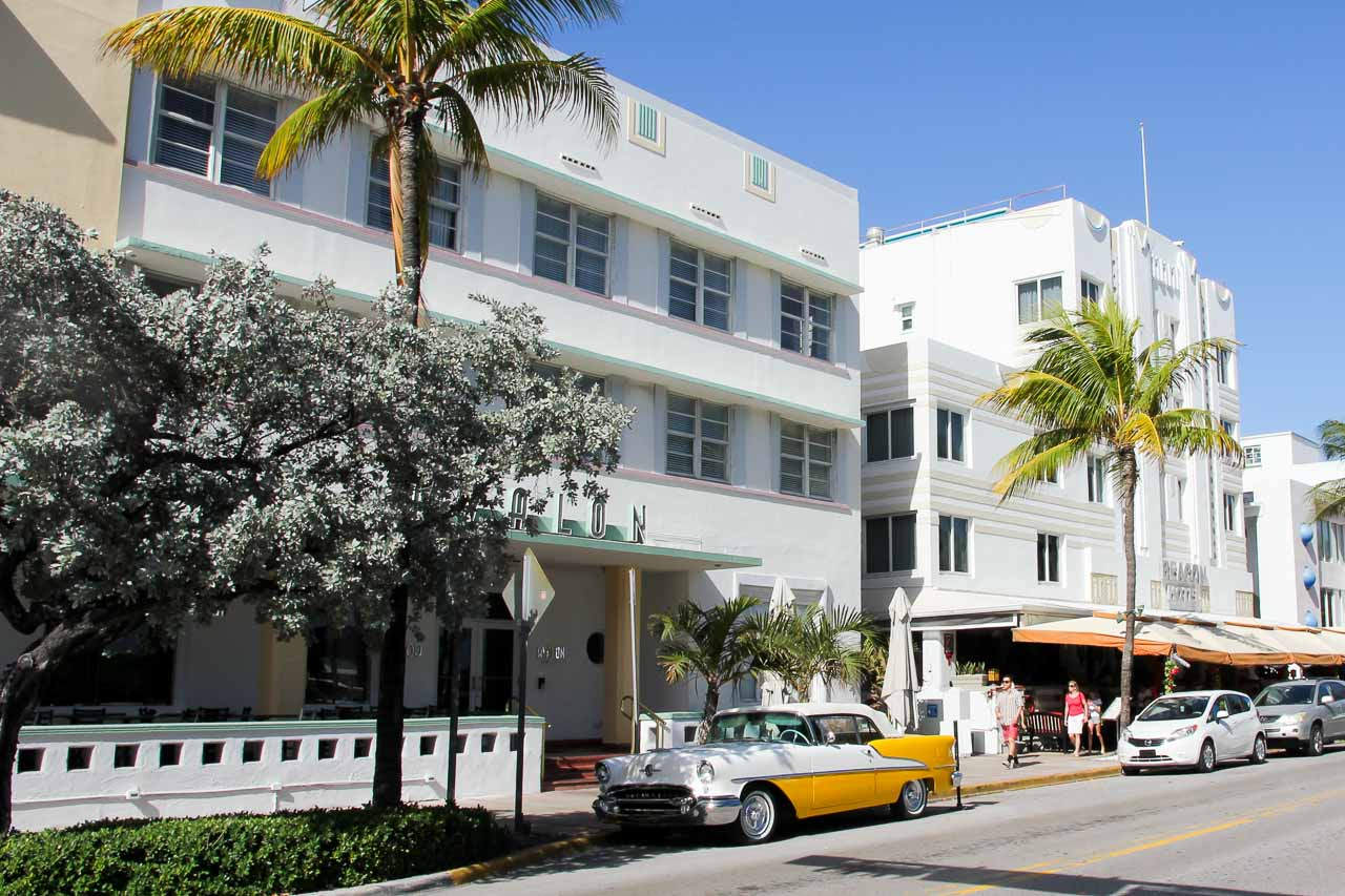 White-washed art deco hotels with palm trees and a vintage car