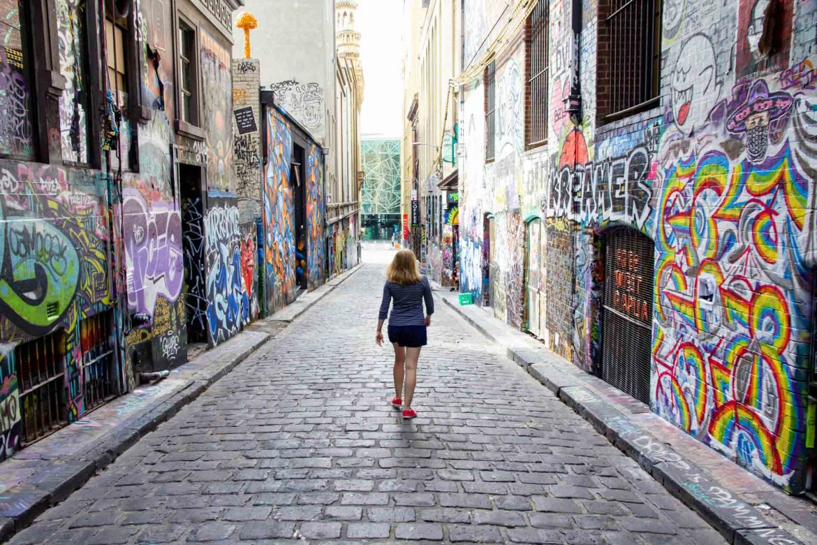 Woman walking down a laneway of Melbourne street art