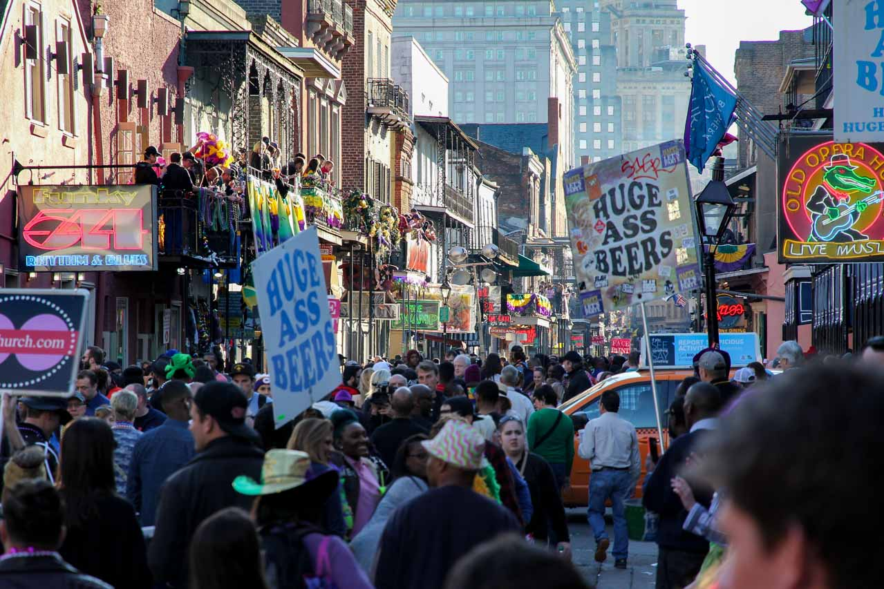 """Crowds in Bourbon street with signs saying """"Huge Ass Beers"""""""