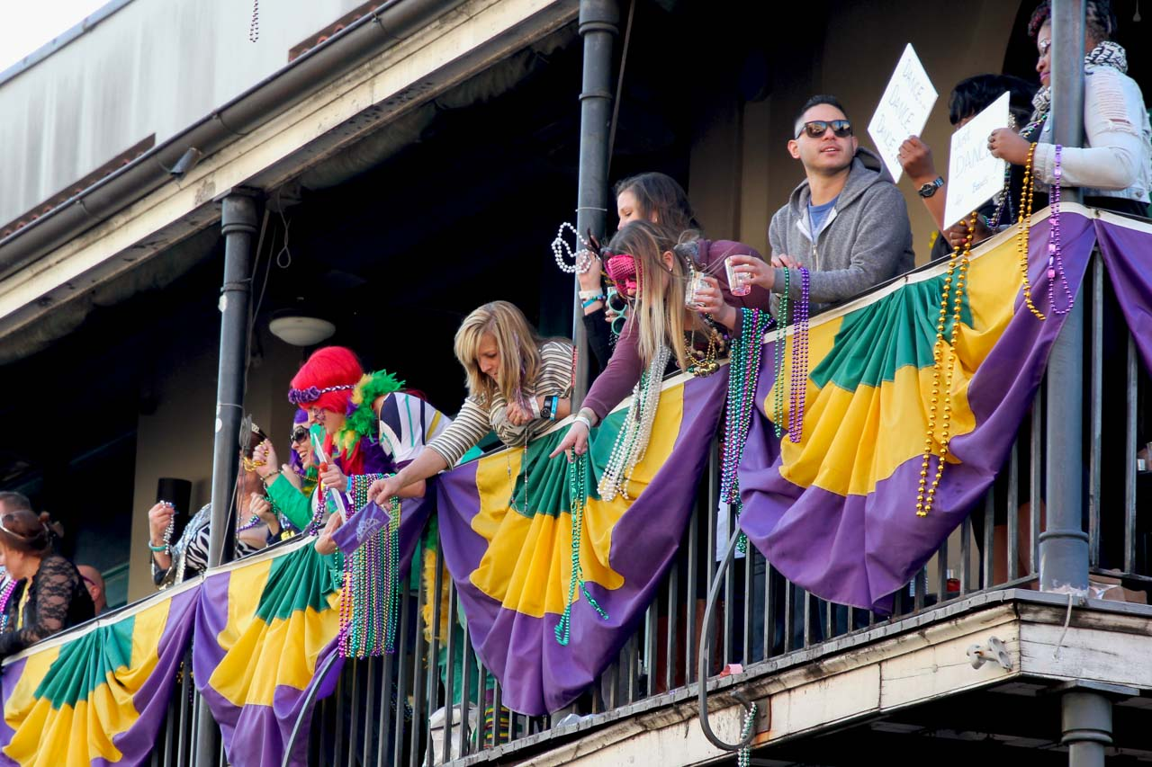People throwing beads from a balcony decorated with purple, yellow and green swagging.