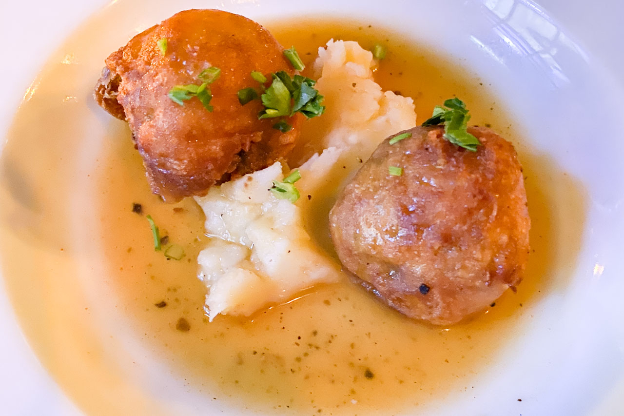 Deep-fried haggis balls with mashed potato and broth
