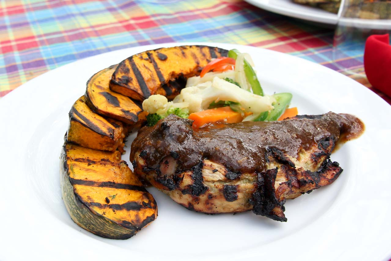 Jerk Chicken and grilled vegetables served on white plate at Jake's Treasure Beach, one of the best places to eat in Jamaica