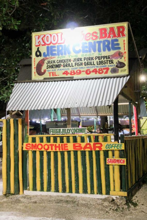 Photo of green and yellow shack advertising Jerk Chicken and smoothie bar