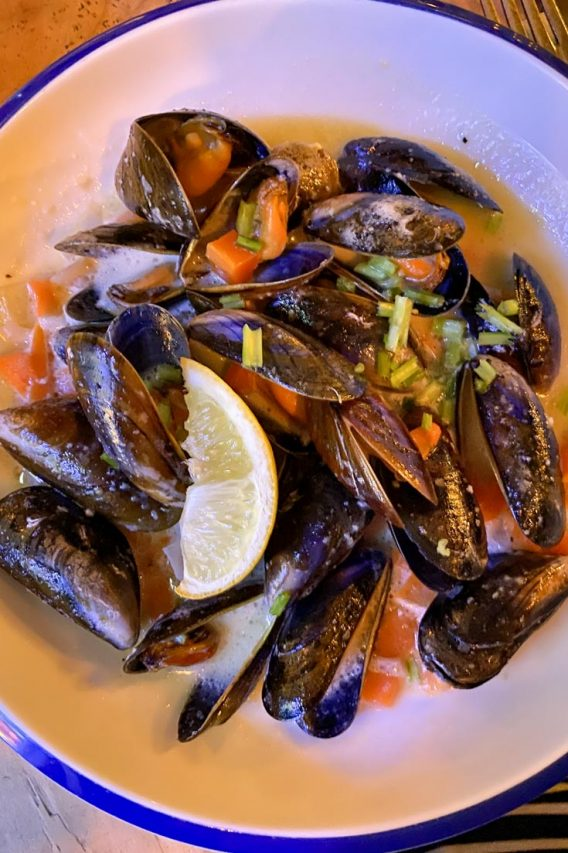 White bowl of muscles in broth with lemon wedge