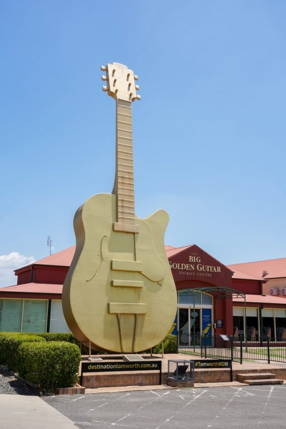 Oversised, gold guitar standing upright infront of red building
