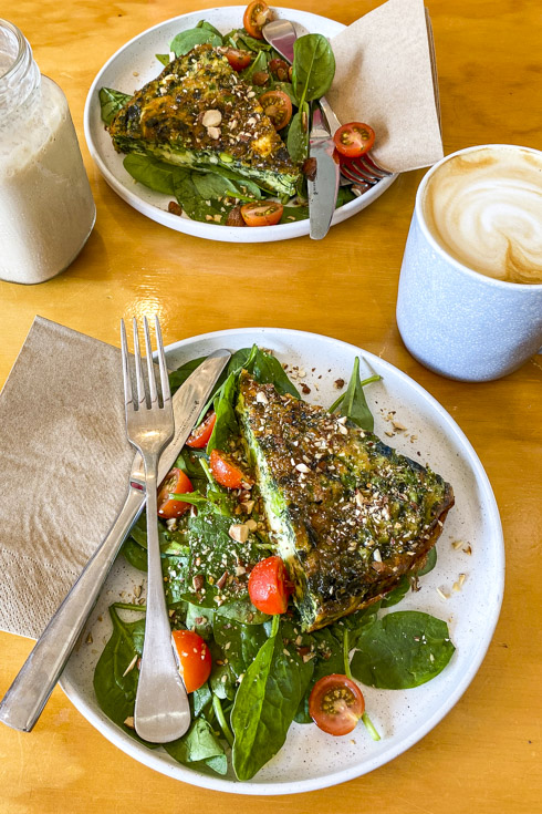 Plates of quiche and salad with coffee