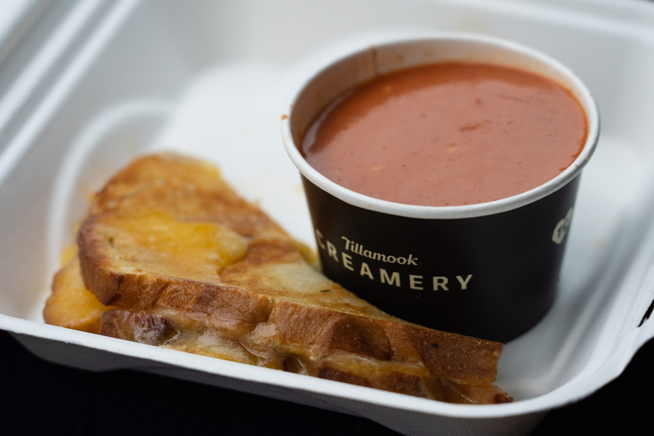Takeout container with grilled cheese sandwich and cup of tomato soup labelled Tillamook Creamery