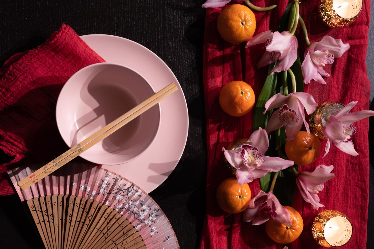Pink bowl with chopsticks and pink folding fan on a dark table with red linen, pink orchids, mandarins and gold tealight candles.