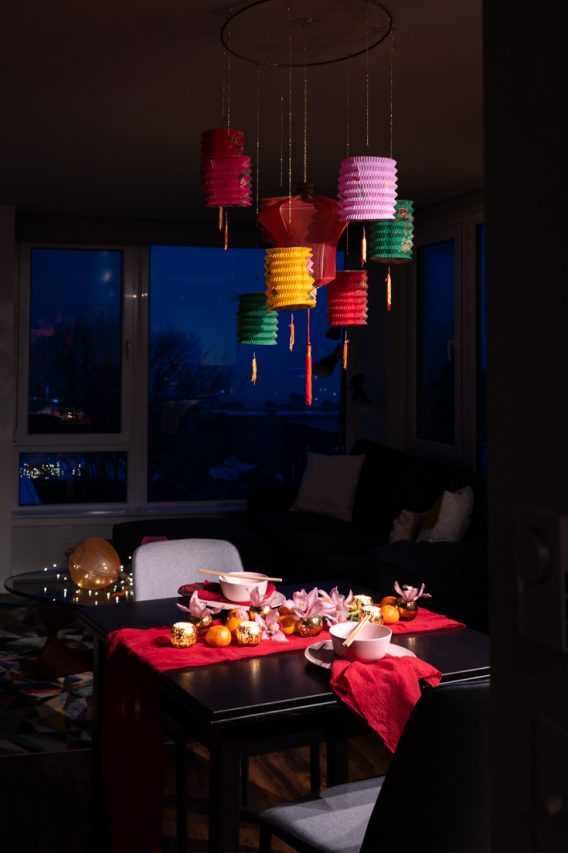 Table set for Chinese New Year dinner in red, pink and gold with colourful paper lanterns hanging above.