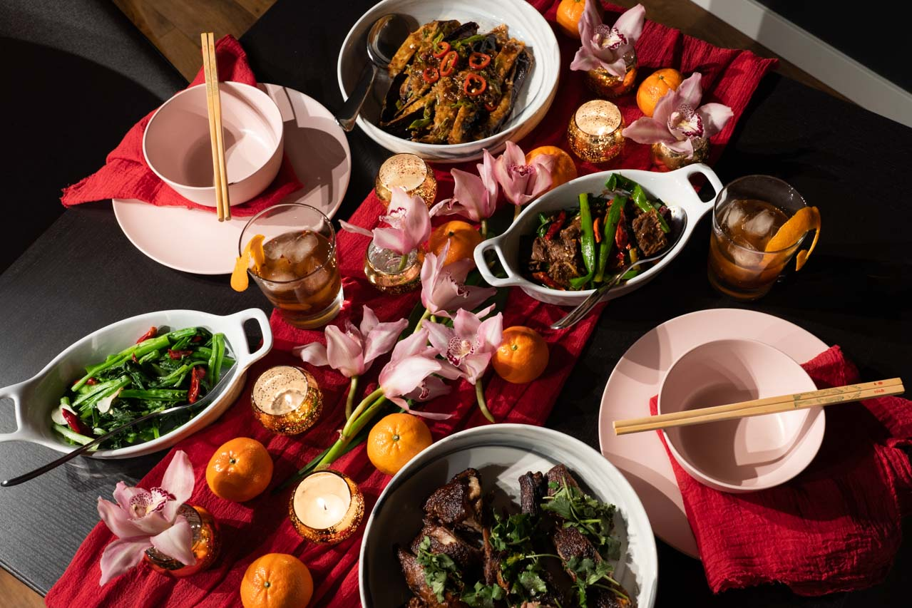 Chinese New Year dinner on a decorated table with pink orchids, mandarins and red table linen.