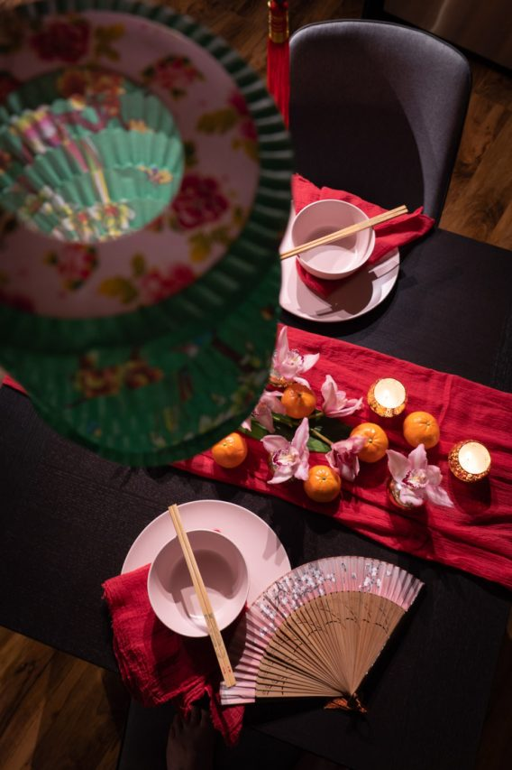 Chinese New Year table decor viewed from above with green, flower-decorated paper lantern above