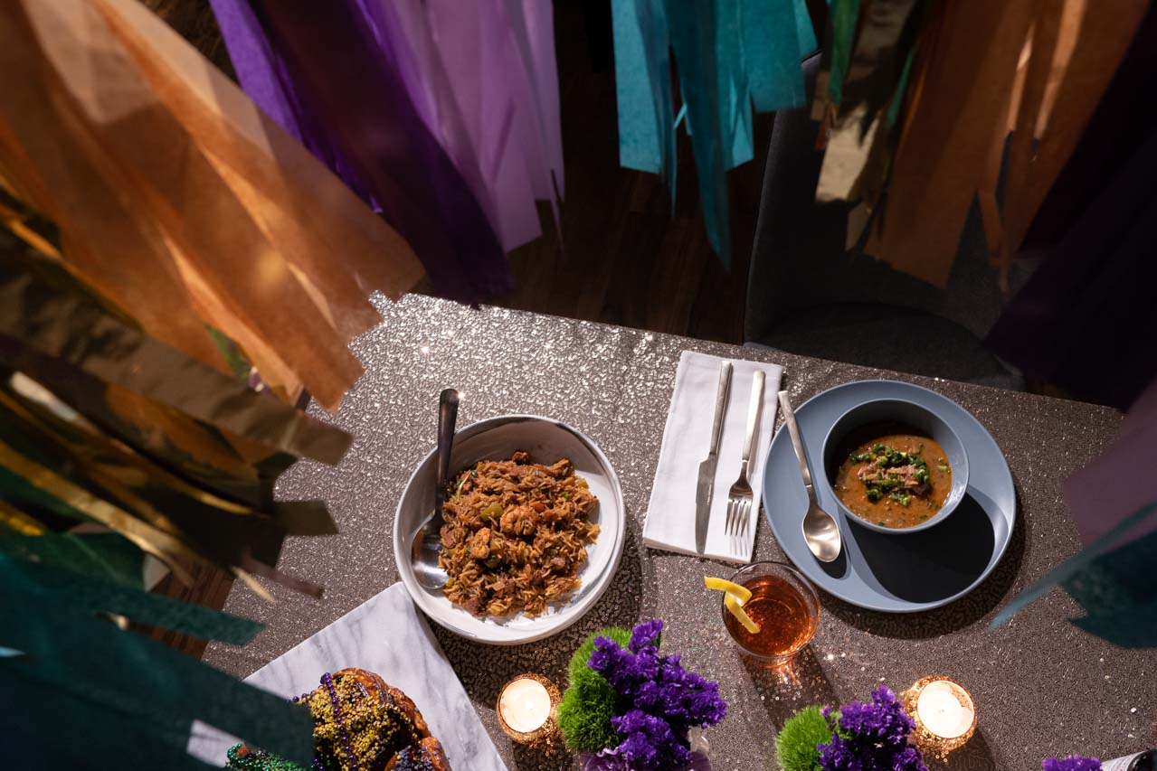 Photo of tabletop with gold sequin tablecloth, purple and green flowers, gold tealight candle holders, plates of gumbo and jambalaya.