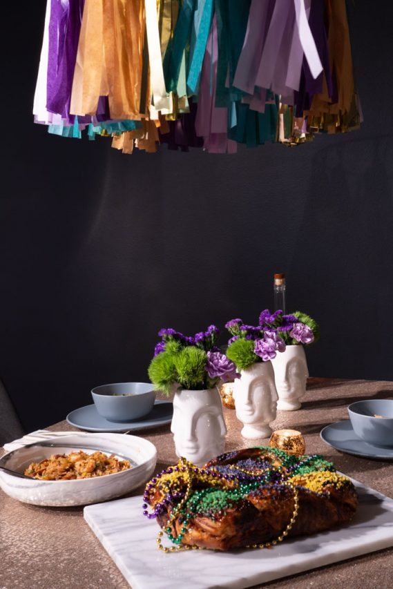 King Cake and bowl of Jambalaya on a table with gold sequin tablecloth and face vases of purple and green flowers.