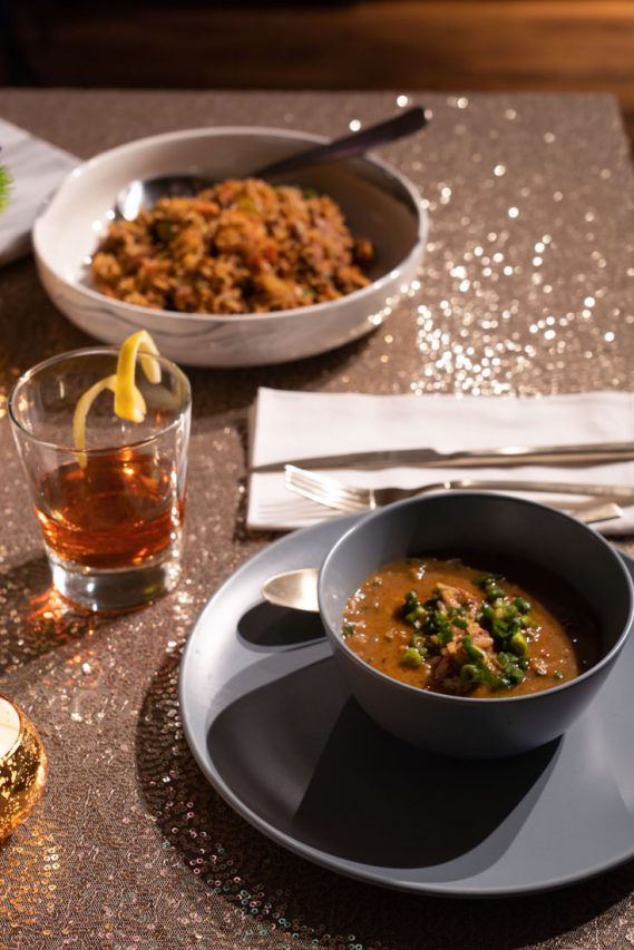 Bowls of gumbo and jambalaya with a cocktail on a gold sequin tablecoth.