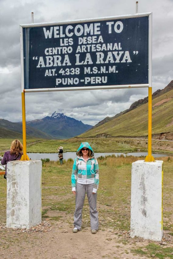 Woman standing infront of roadside sign marking altitude, with mountains in the background