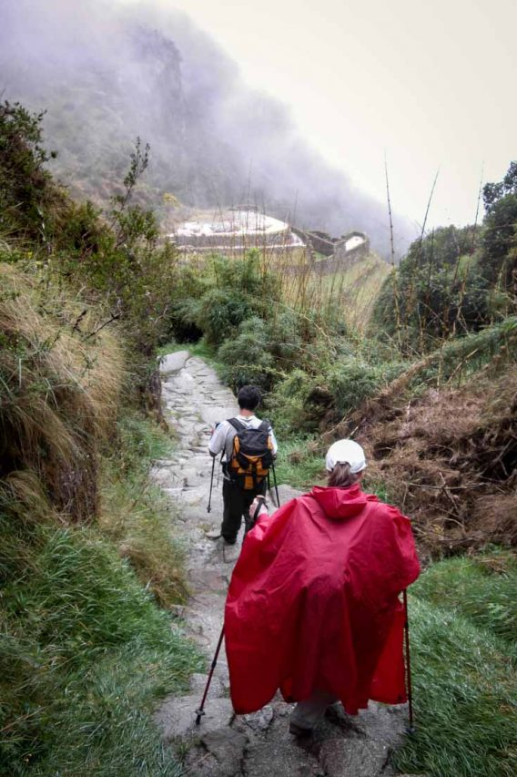 Hikers carefully descending a wet, stone path in the rain