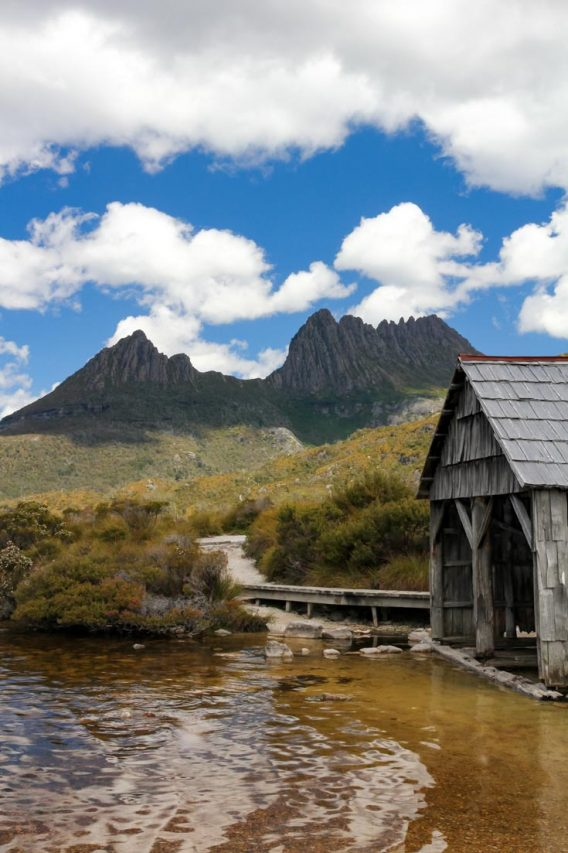 Image of boat shed on edge of lake with jagged mountain behind