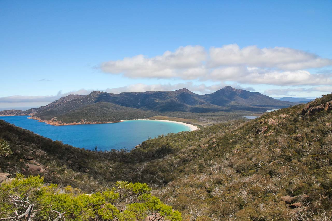 Looking down on mountainous peninsula with a crystal-blue bay and crescent-shaped, sandy beach