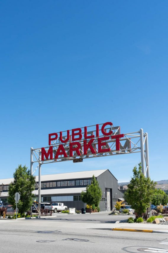 """Photo of red sign reading """"Public Market"""" with large grey shed."""