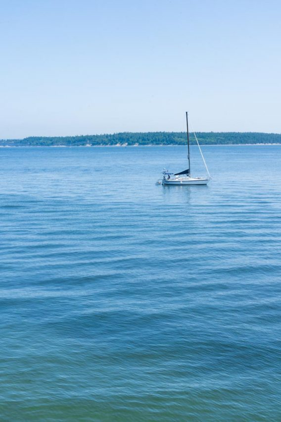 Small yacht moored with blusih-green water and distant island