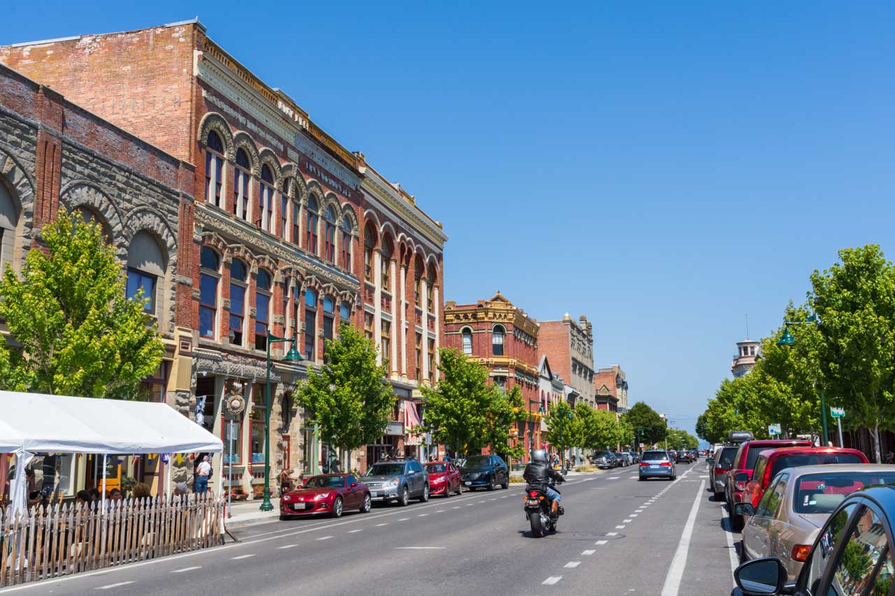 Victorian commercial architecture along road with parked cars and passing motorbike