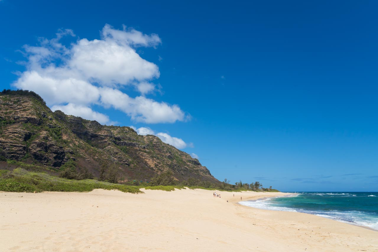Photo of sandy beach with background of mountains tapering to the the water