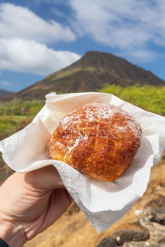 Hand holding malasada with Koko Crater in background