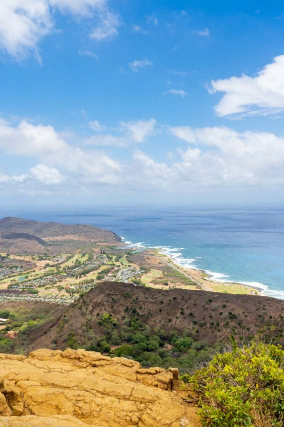View over volcanic crater down to coastline with blue sky and clouds