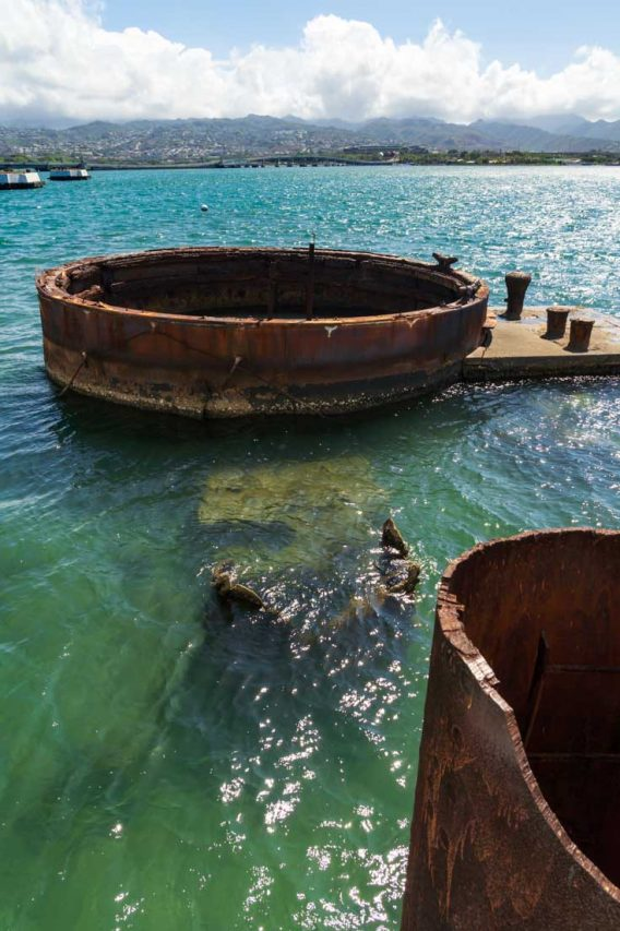 Rusted, sunken remains of ship protruding from blue-green waters