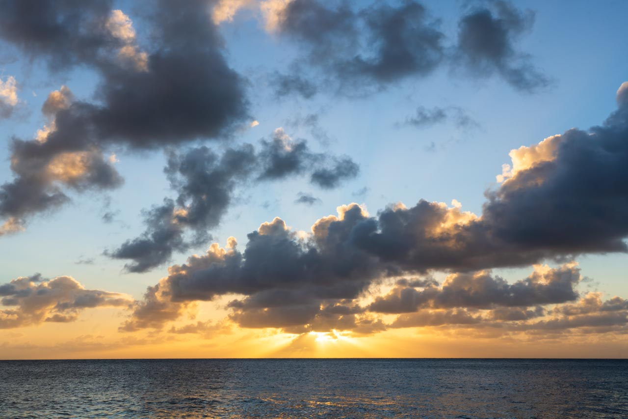 View of sun setting over ocean with clouds in the foreground