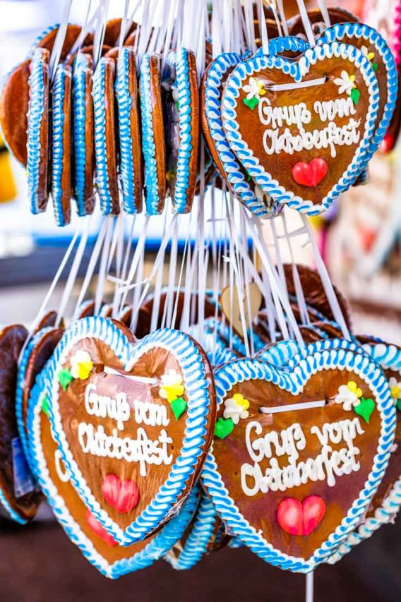 """Gingerbread hearts hanging in a cluster with """"Greetings from Oktoberfest"""" written in icing on them."""