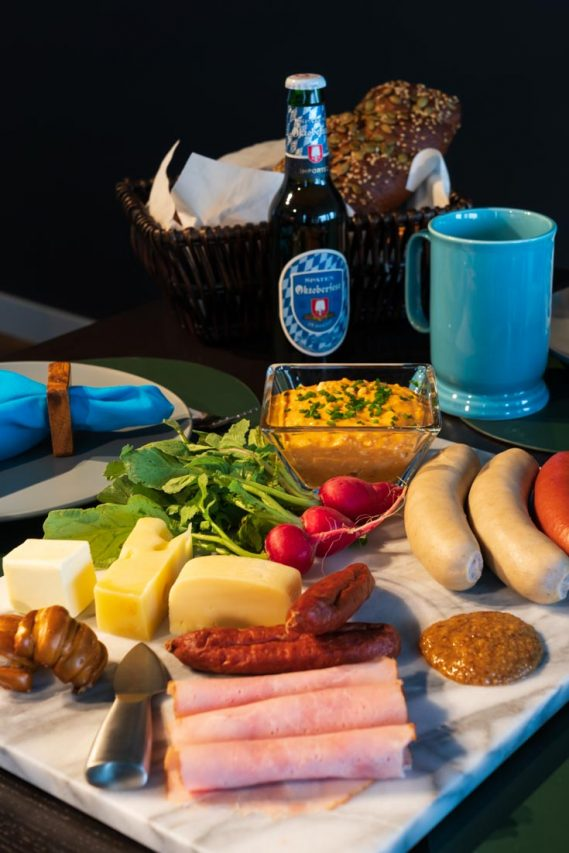 A marble platter with meats, cheeses and radishes