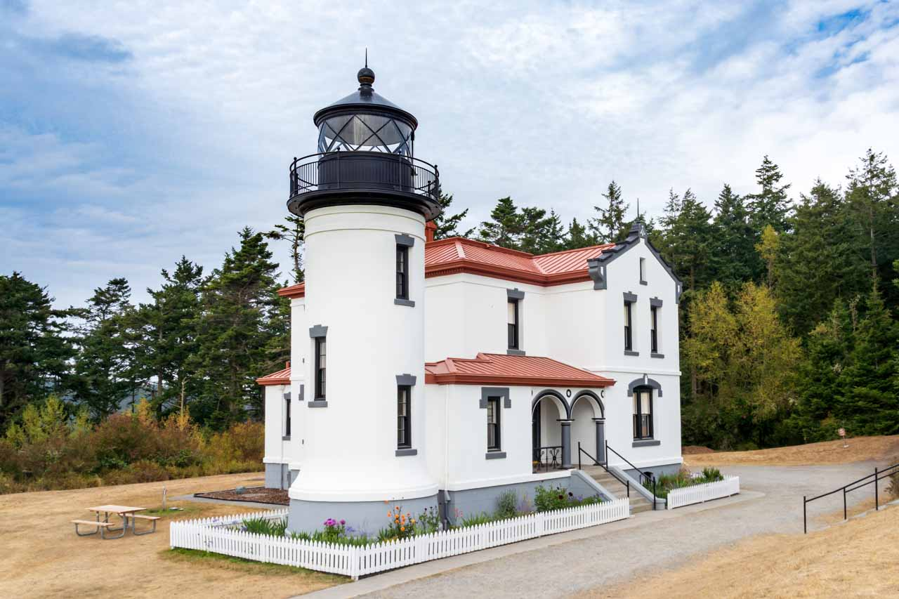 A small, white-washed, historic lighthouse against a backdrop of trees