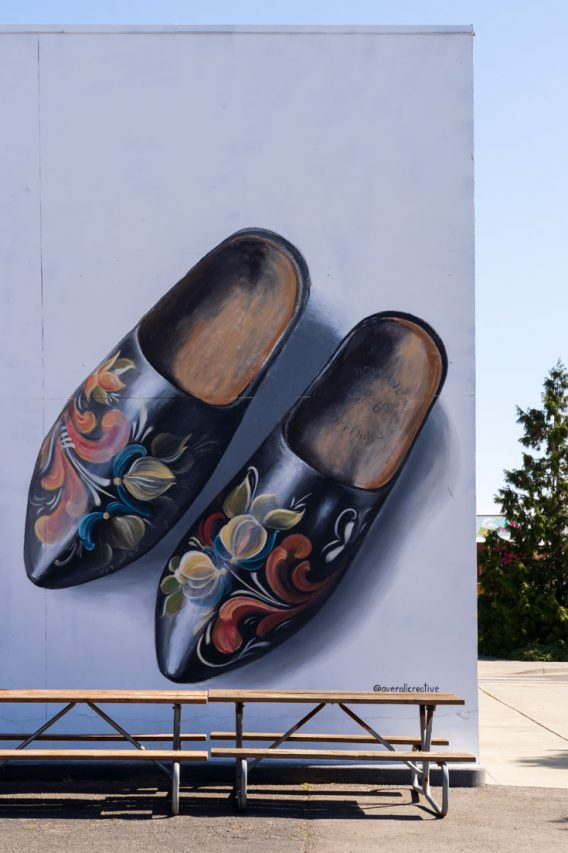 Mural of a pair of wooden clogs on white wall with picnic tables in foreground